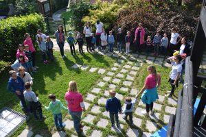 Skupina strokovnih delavcev in otrok stoji na vrtu Centra IRIS. Postavljeni so v krogu.
