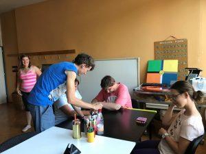 Udeleženci tabora za mizo v učilnici za orientacijo. Se smejijo.