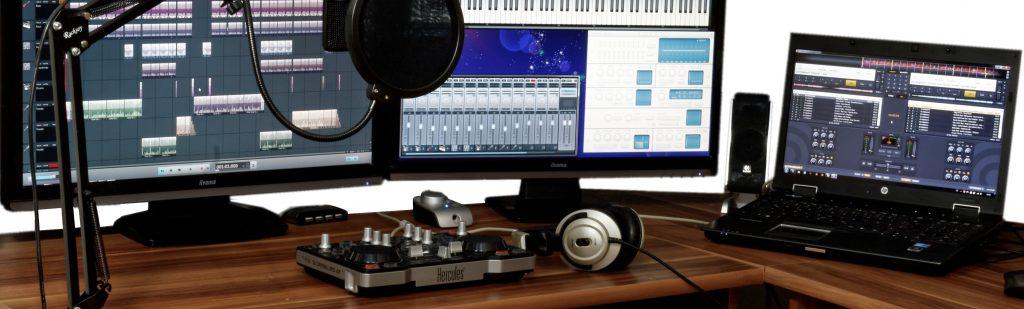 Fotografija radijskega studia: 3 računalniški ekrani in slušalke, mikrofon.