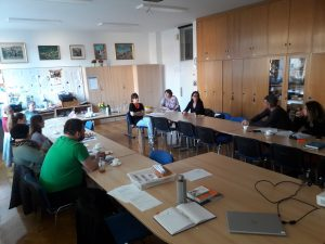 Udeleženci šole sedijo za mizo v zbornici Centra IRIS. Mize so v ovalu. Debata.